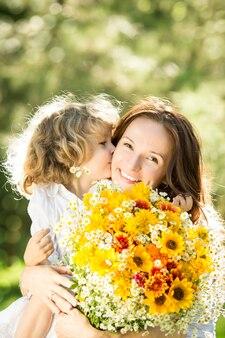 Семья с большим букетом весенних цветов. ребенок целует женщину. концепция дня матери