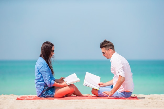 Family with books on the seashore lying