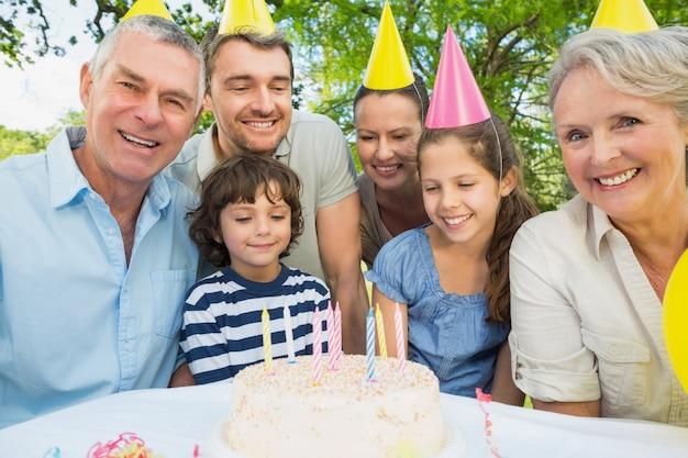 Семья с тортом на открытом воздухе
