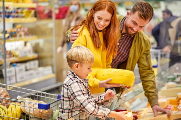 Family with child boy in grocery store, family in shop. parent and children in a mall choosing meal. healthy food.