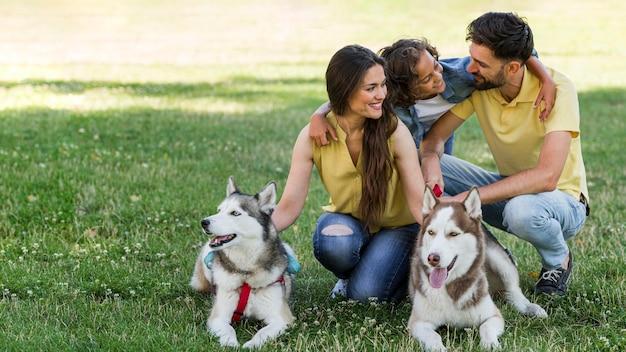 Famiglia con bambino e cani insieme all'aperto