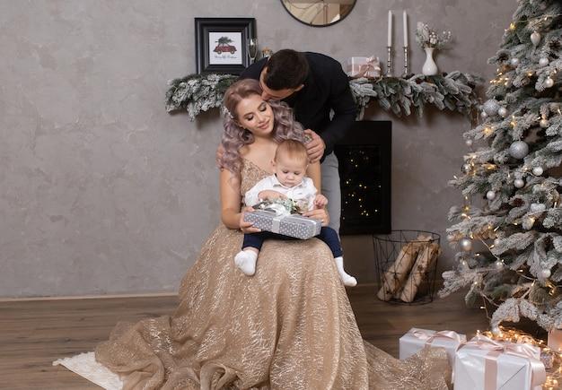 장식된 크리스마스 트리 근처에서 집에서 함께 시간을 보내는 아이를 둔 가족