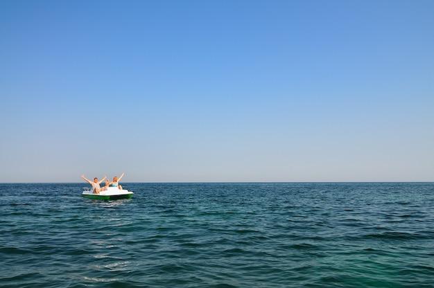 白いカタマランに座って、晴れた夏の日に日光を楽しんでいる子供と家族。幸福、休暇、自由の概念