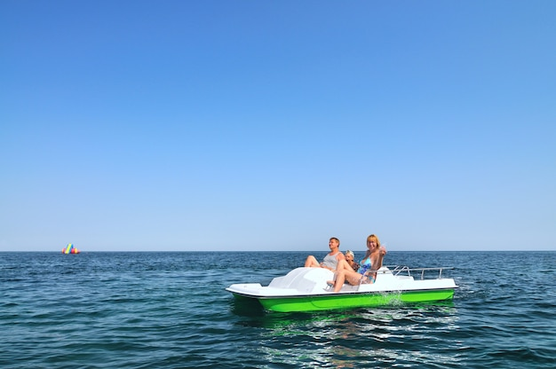 흰색 뗏목에 앉아서 화창한 여름 날에 햇살을 즐기는 아이와 가족. 행복, 휴가 및 자유 개념
