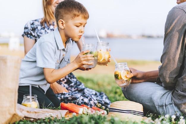 Семья с ребенком летний пикник на природе. маленький мальчик держит желтые и зеленые очки.