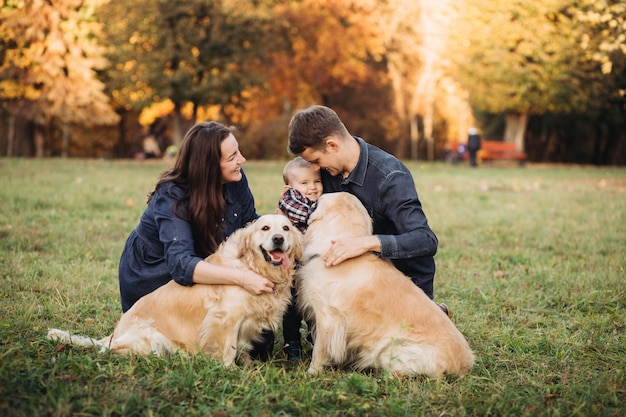 Family with a child and two golden retrievers in an autumn park