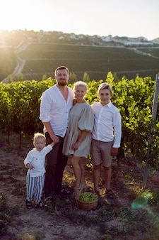 子供、男の子と家族は、緑のベリーのバスケットと日没時にブドウ畑に立っています