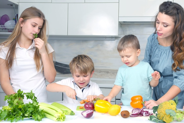 Family with children cut vegetables for cooking.  help children in cooking a home dinner