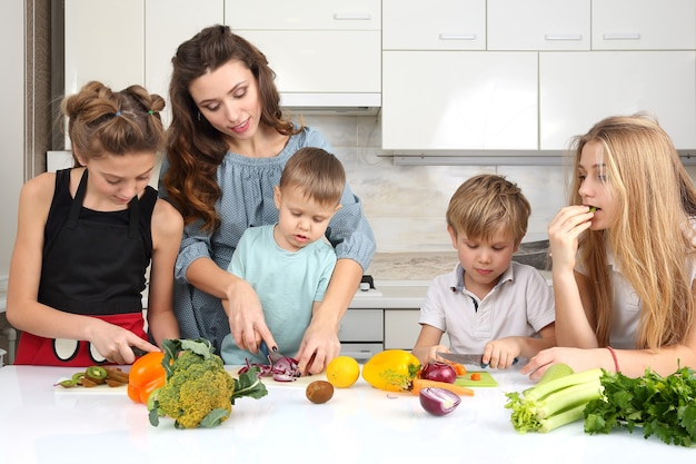 Family with children cut vegetables for cooking