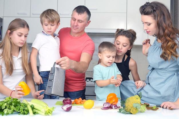 子供連れの家族は料理のために野菜を切ります。子供たちが家で夕食を作るのを手伝う