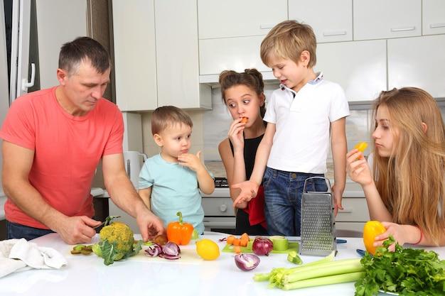 子供連れの家族は料理のために野菜を切る