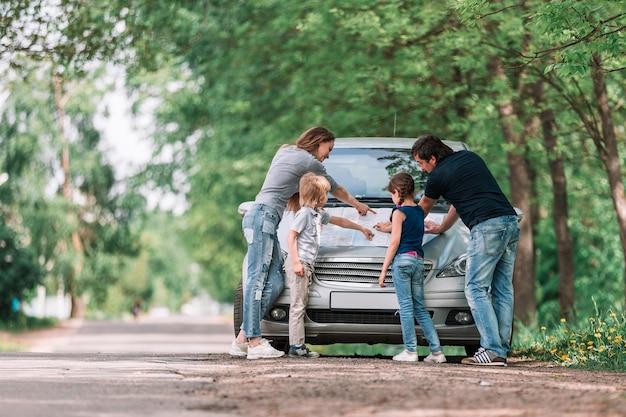 자녀가있는 가족은 가족 여행 중에 종이 카드에 대해 설명합니다.
