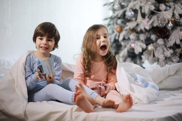 A family with children having fun on the bed under the covers during the christmas holidays.