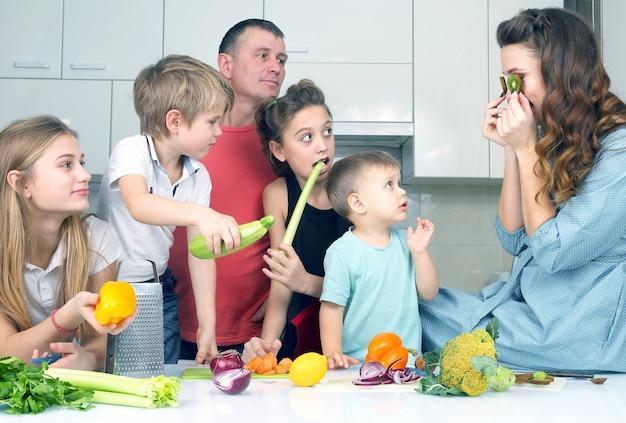 Семья с детьми, веселятся над приготовлением пищи. помочь детям приготовить домашний обед