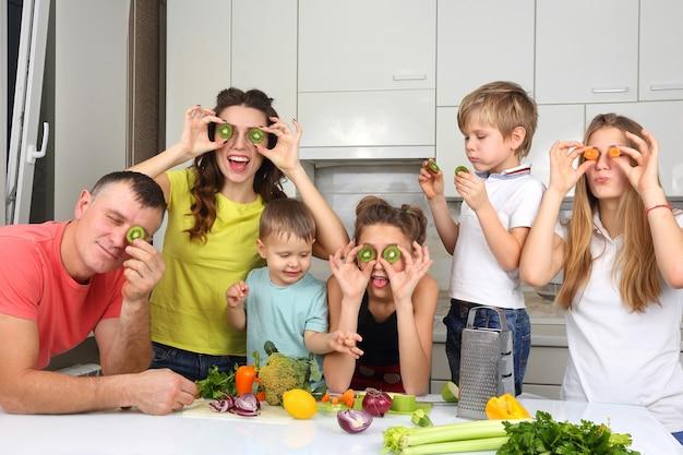 Семья с детьми, веселятся над приготовлением пищи