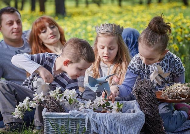 暖かい春の日にピクニックに子供連れの家族。家族の休日の概念