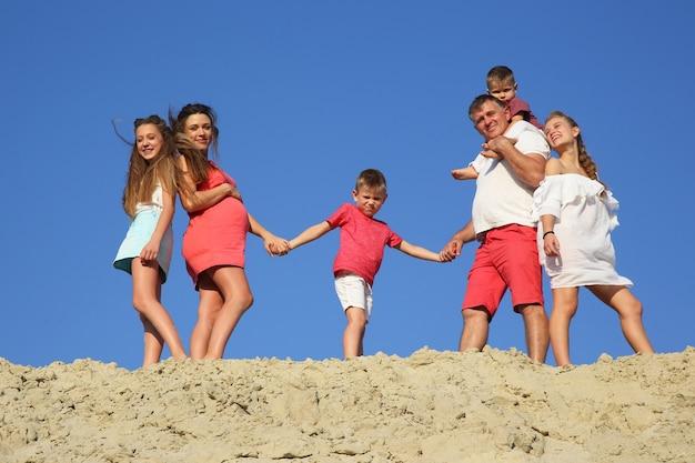 Семья с детьми, стоящими вместе на песчаном холме