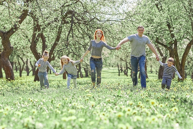 Family with children walking on the grass in the spring garden. good time