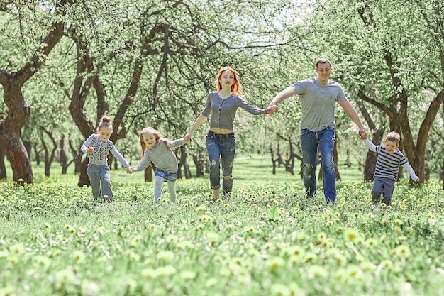 봄 정원에서 잔디에 걷는 아이들과 가족. 좋은 시간