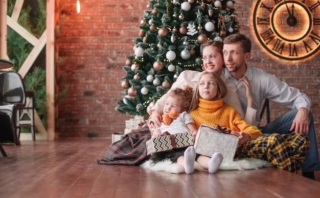居心地の良いリビングルームでクリスマスプレゼントを持っている家族