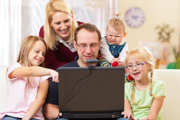 Семья с компьютером с видео-конференцией