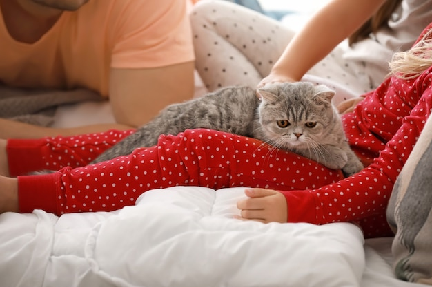 Family with cute cat on bed at home