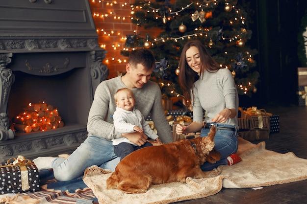 クリスマスツリーの近くに家でかわいい犬と家族