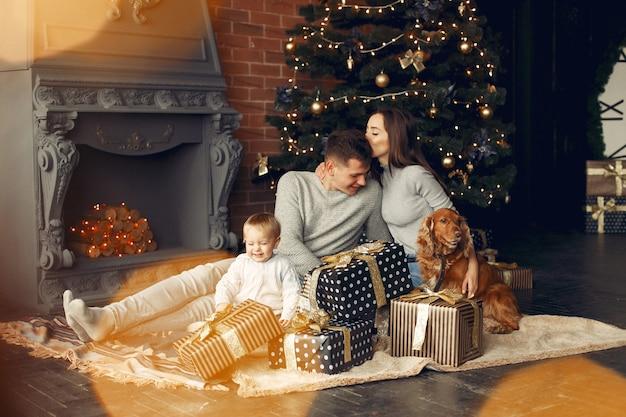 크리스마스 트리 근처 집에서 귀여운 강아지와 가족
