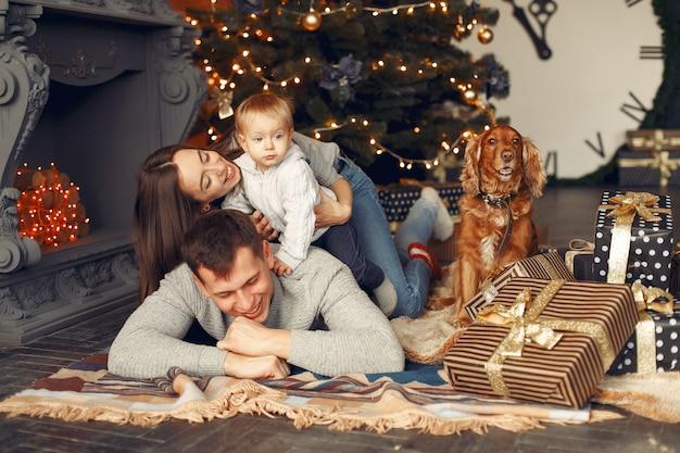 Семья с милой собакой дома возле елки Бесплатные Фотографии