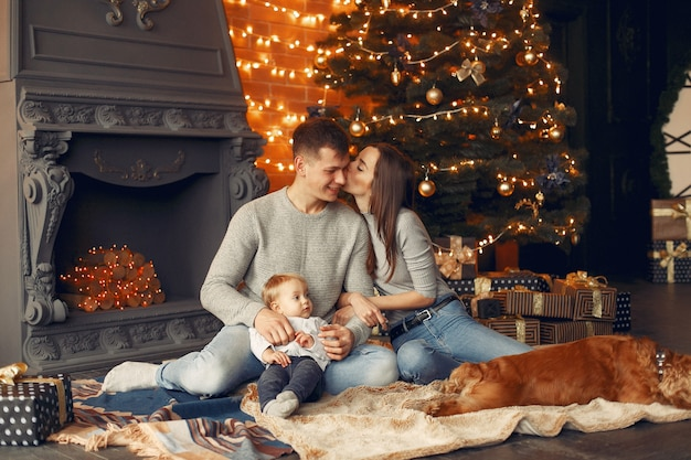 Family with cute dog at home near christmas tree
