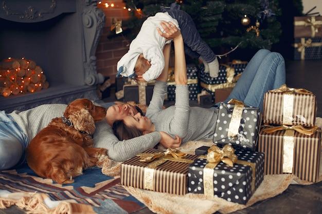 Famiglia con simpatico cane a casa vicino all'albero di natale