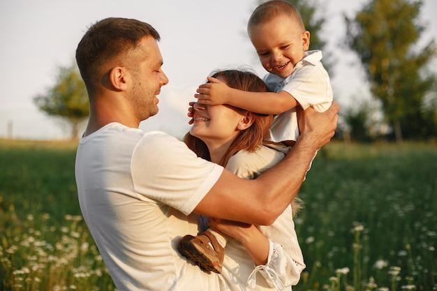 かわいい小さな子供を持つ家族。白いtシャツを着た父。夕日の背景。