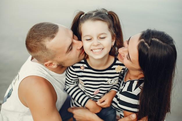 Семья с дочерью, играя на песке