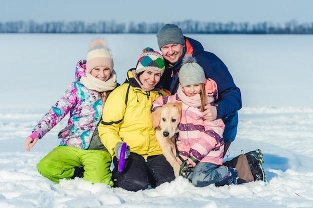 Семья с собакой на зимней прогулке