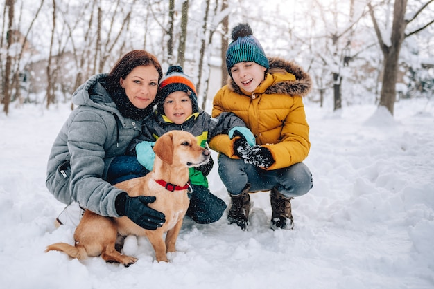 Family with dog playing in the snow