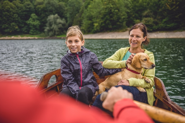 Family with dog rowing on a mountain lake