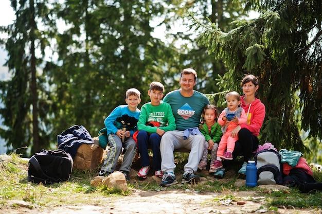 山で休んでいる4人の子供を持つ家族。子供と一緒に旅行やハイキング。