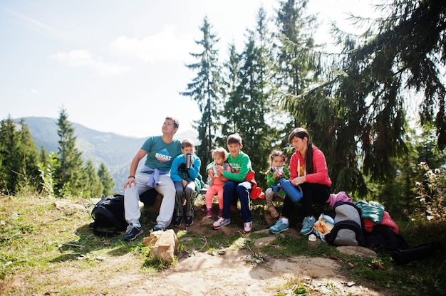 Family with four kids resting in mountains. travel and hiking with childrens.