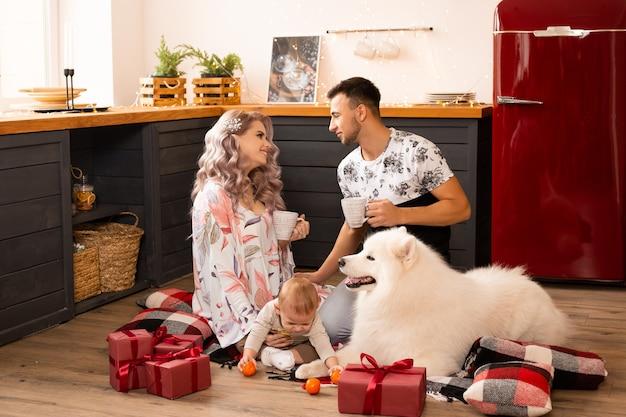 クリスマスの時期に家で一緒に時間を楽しんでいるギフトボックスと犬のサモエドを持つ家族