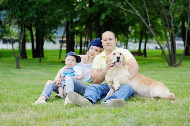 Family with a golden retriever dog on the grass