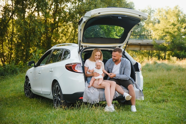 Семья с ребенком, сидящим в багажнике автомобиля