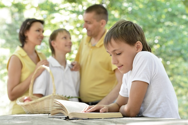 Family with kids and book outdoors in summer