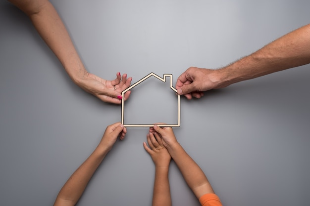 Family with kids holding the framework of a house on a gray background