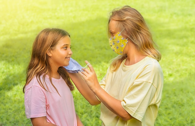 屋外の公園でフェイスマスクで子供連れのご家族。母と子は、コロナウイルスとインフルエンザの発生中にフェイスマスクを着用します。ウイルスと病気からの保護