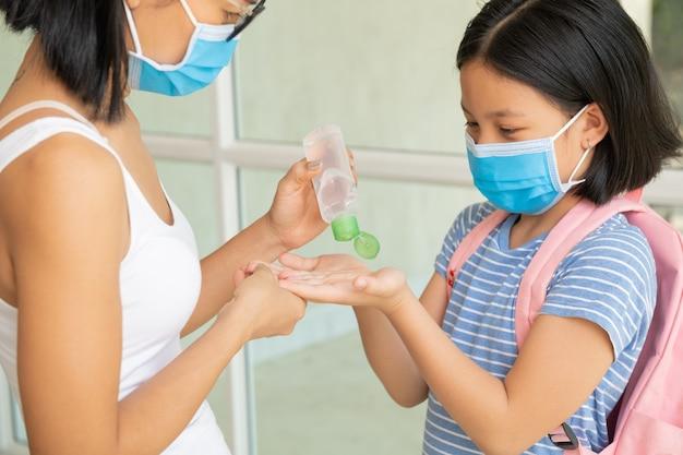 フェイスマスクで子供と家族。母と子は、コロナウイルスとインフルエンザの発生時にフェイスマスクを着用します。ウイルスと病気の保護、公共の混雑した場所での手指消毒剤。
