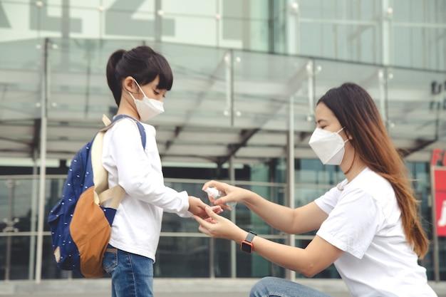 쇼핑몰에서 안면 마스크를 쓴 아이들이 있는 가족. 엄마와 딸은 코로나바이러스와 독감이 발병하는 동안 안면 마스크를 착용합니다. 바이러스 및 질병 보호, 공공 장소에서 손 소독제.