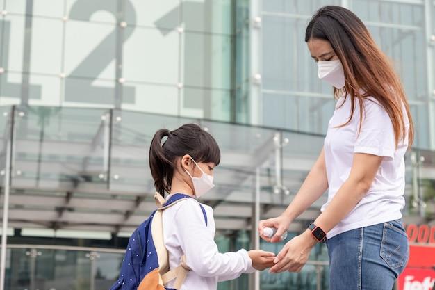 쇼핑몰에서 안면 마스크를 쓴 아이들이 있는 가족 엄마와 딸은 안면 마스크를 착용합니다