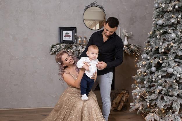 クリスマスツリーの近くのリビングルームで自宅で一緒に時間を楽しんでいる小さな男の子と家族
