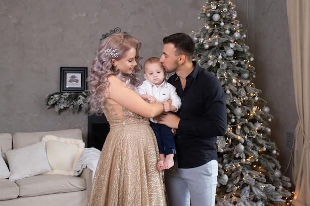 크리스마스 트리 근처에서 집에서 함께 시간을 보내는 어린 소년을 동반한 가족