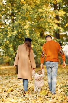Famiglia con la piccola figlia in un parco di autunno